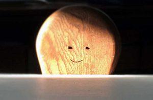 目と口がついている木製の椅子の背もたれ