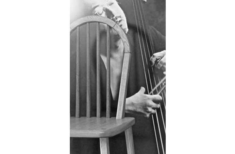 ハープの形の背もたれの椅子とベースを弾いている人の写真