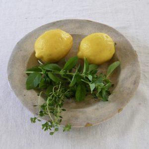 陶器の皿に乗ったレモン2個とミントとタイム