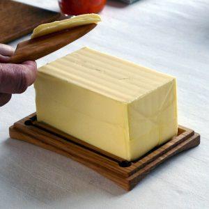 ポンドサイズ木製バターケース に置かれたバターを木製バターナイフで削る